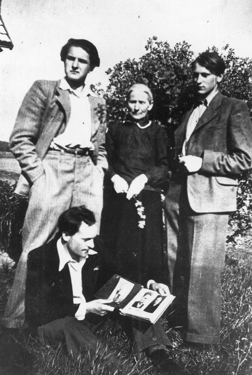 Adolfas Mekas, Mekų motina, Jonas ir Petras Mekai.<br />  Petras laiko šeimos fotografijų albumą.<br />  1943 m.