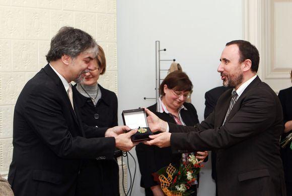 """Kultūros ministras Arūnas Gelūnas įteikia Petrui Geniušui Kultūros ministerijos garbės ženklą """"Nešk savo šviesą ir tikėk""""."""