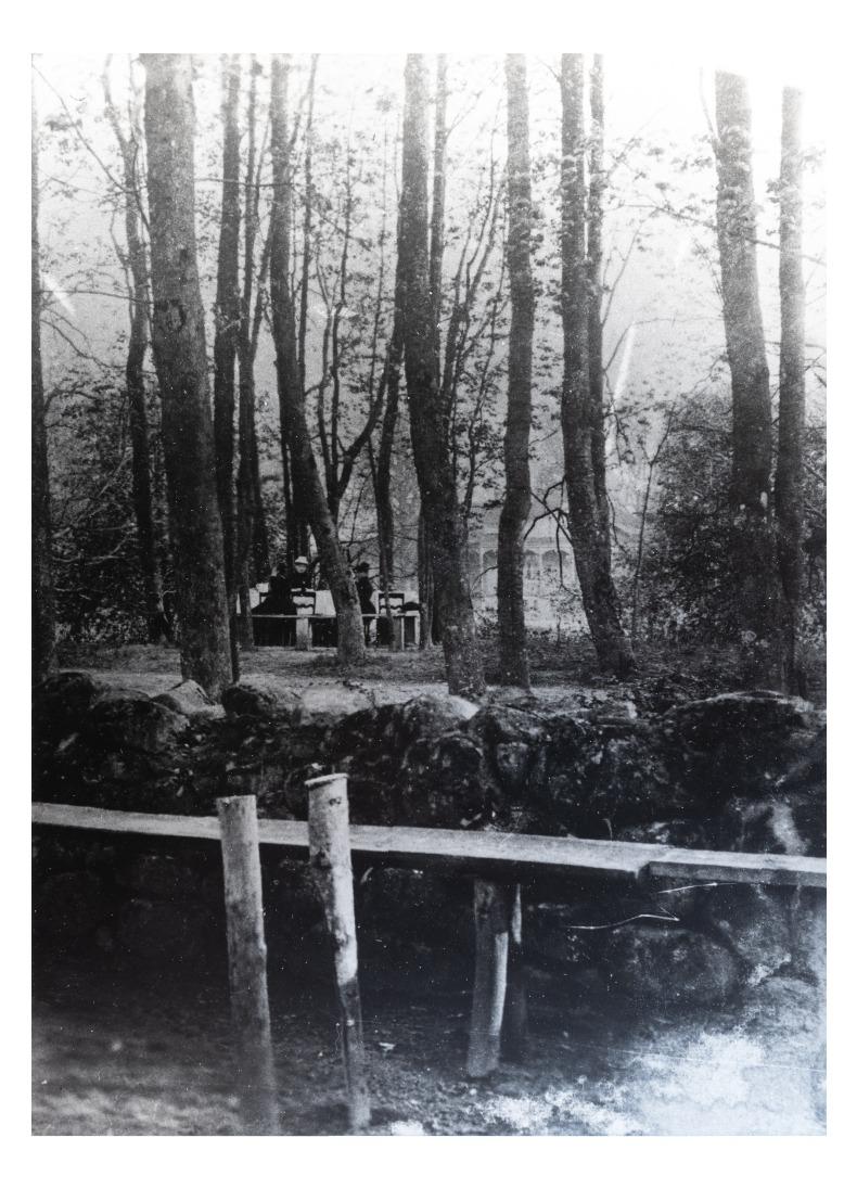 """Kretingos dvaro parko kampelis. Tolumoje – medinė dvaro oficina (kopija). P. Mongirdaitės albumas """"Kretynga"""", p. 23., 1890 m."""