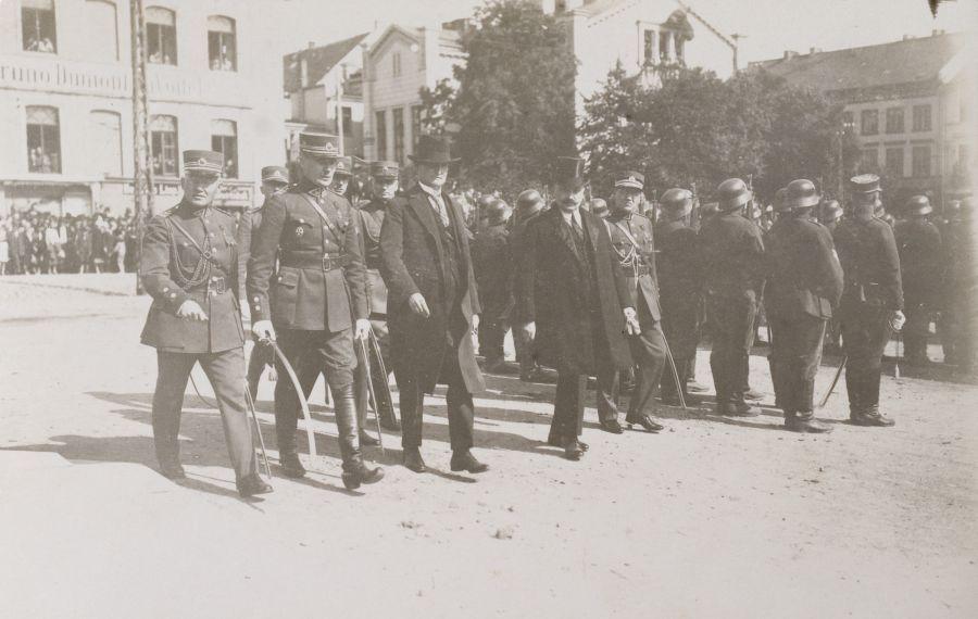 Prezidentas ir jo palyda atvyksta į Teatro aikštę stebėti karinio parado. Iš kairės 2-as – 7-ojo pėstininkų Žemaičių kunigaikščio Butigeidžio pulko vadas plk. Petras Genys. Klaipėda, 1926 m. rugpjūčio 29 d.