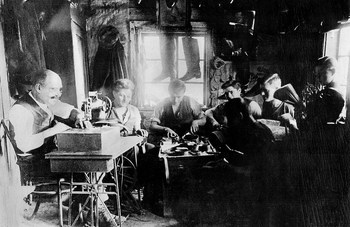 Žeimelio batsiuvio Juozo Dambrausko (kairėje) dirbtuvėje (Julius Juzeliūnas sėdi priekyje), apie 1930 m.