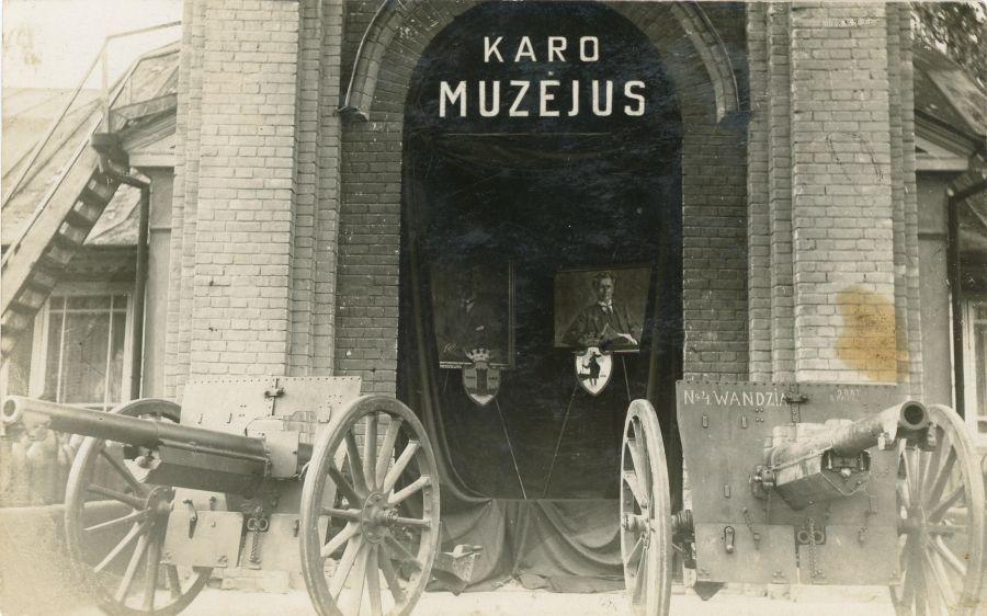 Karo muziejaus centrinis įėjimas, papuoštas Lietuvos Respublikos Prezidentų Aleksandro Stulginskio ir K. Griniaus portretais, naujai išrinkto Lietuvos Respublikos Prezidento apsilankymo muziejuje proga. Kaunas, 1926 m. birželio 8 d.