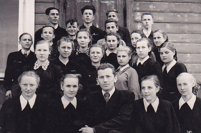 Devintos klasės mokinys B. Radzevičius (paskutinėje eilėje antras iš dešinės) su klasės draugais ir mokytoju. Paskutinėje eilėje pirmas iš dešinės – A. Masionis. 1958 m., Vyžuonos.